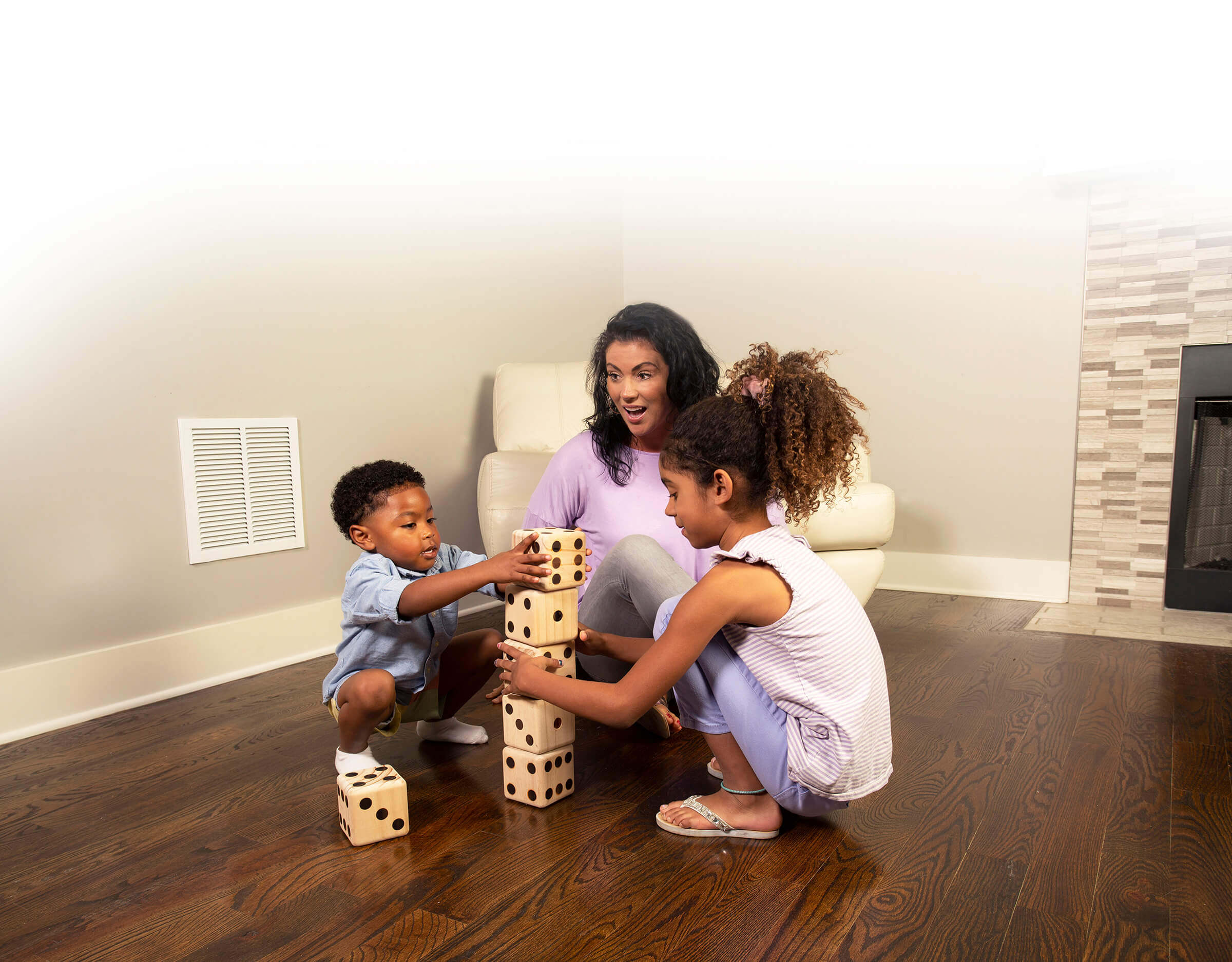 Mom and children playing on wood floors in Fort Smith